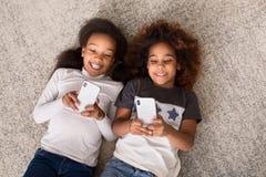 Gelukkige meisjes met smartphones die op vloer liggen stock afbeeldingen