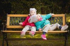 Gelukkige meisjes op een bank in het hout Royalty-vrije Stock Afbeelding
