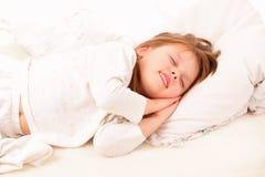 Gelukkige meisjeslaap in bed Royalty-vrije Stock Afbeeldingen