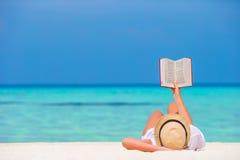 Gelukkige meisjeslezing tijdens tropisch wit strand Royalty-vrije Stock Foto's