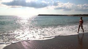 Gelukkige meisjeslooppas langs het strand stock footage