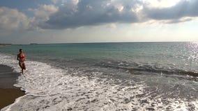 Gelukkige meisjeslooppas langs het strand stock videobeelden