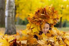 Gelukkige meisjespelen met de herfstbladeren in het park royalty-vrije stock foto's