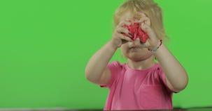 Gelukkige meisjespelen met plasticine op chroma zeer belangrijke achtergrond stock video