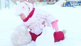 Gelukkige meisjespelen met sneeuw op speelplaats bij de winter zonnige dag stock footage