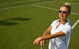 Gelukkige meisjestribunes met racket op hof bij zonnige de zomerdag Stock Foto's