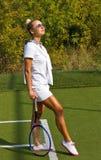 Gelukkige meisjestribunes met racket op hof bij zonnige de zomerdag Stock Afbeelding