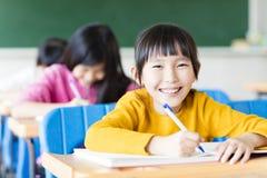 Gelukkige meisjestudent die in het klaslokaal bestuderen stock afbeeldingen