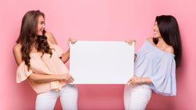 Gelukkige meisjesvrienden die leeg reclamebord houden stock fotografie