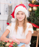 Gelukkige meisjeszitting bij de lijst en het schrijven Nieuwjaar en Kerstmisgelukwens in prentbriefkaar Royalty-vrije Stock Afbeelding
