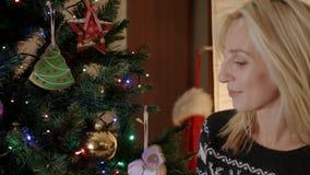 Gelukkige meisjeszitting onder de nieuwe jaarboom en het bekijken speelgoed stock video