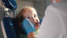 Gelukkige meisjezitting die als tandvoorzitter, stomatologist haar tanden onderzoeken stock videobeelden