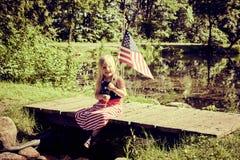 Gelukkige meisjezitting op brug met de vlag van de V.S. stock afbeelding