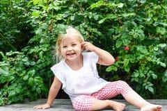 Gelukkige meisjezitting op een bank in de tuin royalty-vrije stock fotografie