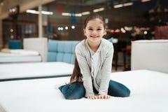 Gelukkige meisjezitting op matras in matrasopslag Het kiezen van matras in opslag stock afbeelding