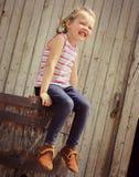 Gelukkige meisjezitting op oud vat stock afbeelding