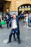 Gelukkige mens buiten Flinders-Straatpost na de Kop van Melbourne Stock Foto