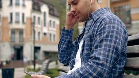 Gelukkige mens die aan muziek van een slimme telefoon met een de stadsachtergrond van de warmtezonsondergang luisteren stock video