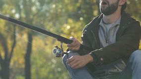 Gelukkige mens die actief zijn hengel bewegen en lijn, vissen winden die, hobby bijten stock footage