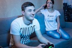 Gelukkige mens die een videospelletje spelen terwijl zijn meisje die spreken Royalty-vrije Stock Fotografie
