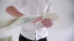 Gelukkige Mens die geld op een witte achtergrond werpen Langzame Motie stock footage