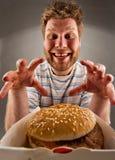 Gelukkige mens die hamburger voorbereidingen treft te eten Royalty-vrije Stock Foto's