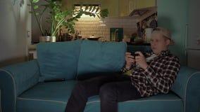 Gelukkige mens die het spel op zijn mobiel spelen terwijl het liggen op de laag 4K stock footage