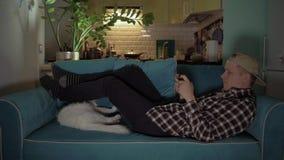 Gelukkige mens die het spel op zijn mobiel spelen terwijl het liggen op de laag met kat 4K stock footage