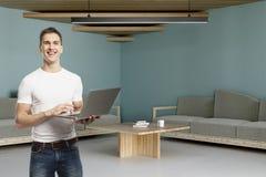 Gelukkige mens die laptop in bureau met behulp van Stock Afbeeldingen