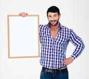 Gelukkige mens die lege raad houden Stock Foto's