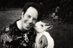 Gelukkige mens die met vriendschappelijke geit glimlachen Stock Foto's