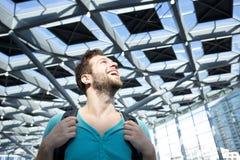 Gelukkige mens die met zak bij luchthaven lachen Royalty-vrije Stock Foto