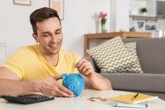 Gelukkige mens die muntstuk zetten in spaarvarken bij lijst in woonkamer stock foto
