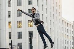 Gelukkige mens die naar of van het werk gaan en naast commercieel centrum dansen stock foto