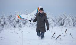 Gelukkige mens die op de sneeuwwinter lopen met het model van het rcvliegtuig stock foto's
