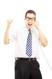 Gelukkige mens die op een telefoon en een gesturing geluk spreekt Stock Foto's