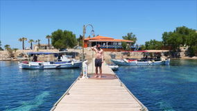 gelukkige mens die op houten pijler bij strand na het zwemmen overgieten stock video