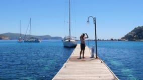 gelukkige mens die op houten pijler bij strand na het zwemmen overgieten stock videobeelden