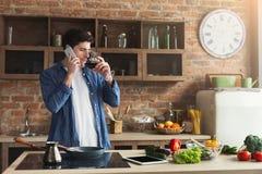 Gelukkige mens die op telefoon en het drinken wijn in keuken spreken stock foto