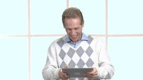 Gelukkige mens die pret het spelen op tablet hebben stock videobeelden