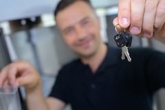 Gelukkige mens die sleutels tonen aan nieuw huis stock fotografie