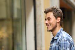 Gelukkige mens die storefront in de straat letten op stock foto's