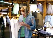 Gelukkige mens die voor kleren bij kledingsopslag winkelen Royalty-vrije Stock Fotografie