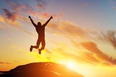 Gelukkige mens die voor vreugde op de piek van de berg bij zonsondergang springen Succes