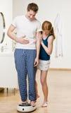 Gelukkige mens die weegt op schalen Stock Fotografie