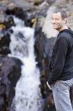 Gelukkige mens die zich door een kleine rotswaterval bevinden royalty-vrije stock foto's