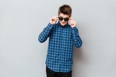 Gelukkige mens die zonnebril dragen die zich over grijze muur bevinden stock fotografie