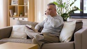 Gelukkige mens het drinken wijn en thuis het lezen van boek stock videobeelden