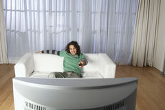 Gelukkige Mens het Letten op Televisie op Bank  Stock Foto's