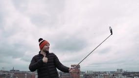 Gelukkige mens, in kleurrijke hoed, die selfie foto met cellphone op dak, 4K neemt stock videobeelden